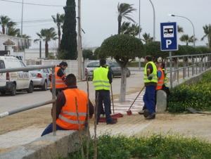Nära oss är sju man sysselsatta med att sopa rent en av infarterna till parkeringsplanen.